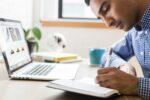 Mand arbejder fokuseret og skriver på notesblog